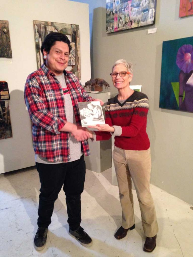 Josh Candelaria gives Adam Sturch artwork to Ruanna Waldrum